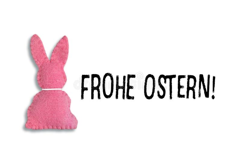 Pink Easter bunny with text `Frohe Ostern` on a white background.Translation: `Happy Easter`. Pink Easter bunny isolated with a white collard  and on the e the stock photography