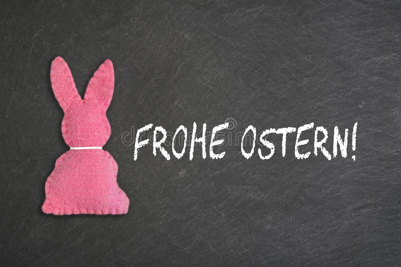Pink Easter bunny with text `Frohe Ostern` on a chalkboard background. Transla. Pink Easter bunny isolated with a white collard  and on the e the text `Frohe stock images