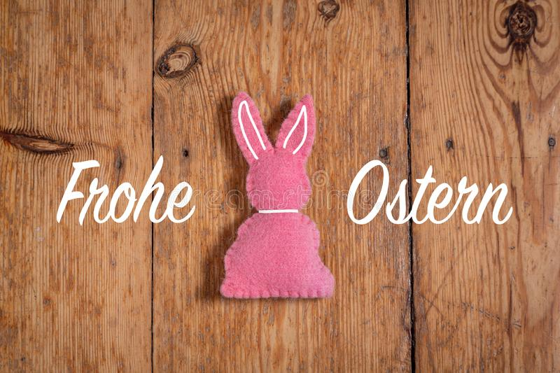 Pink Easter bunny with text `Frohe Ostern` and a wooden background. Translation: `Happy Easter`. Pink Easter bunny with a white collard and ears and a text on royalty free stock images