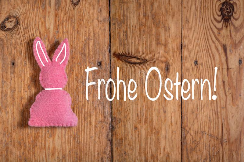 Pink Easter bunny with text `Frohe Ostern` and a wooden background. Translation: `Happy Easter`. Pink Easter bunny with a white collard and ears and a text on royalty free stock photography