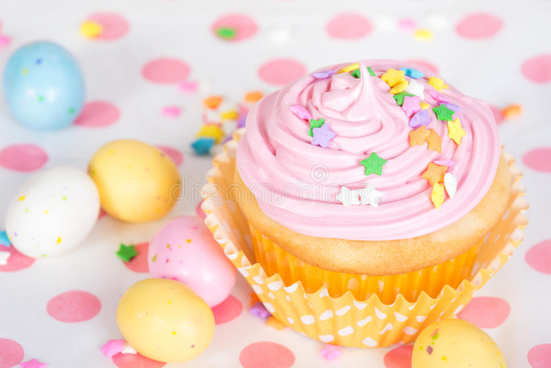 Pink Easter cupcake with candy and sprinkles royalty free stock images
