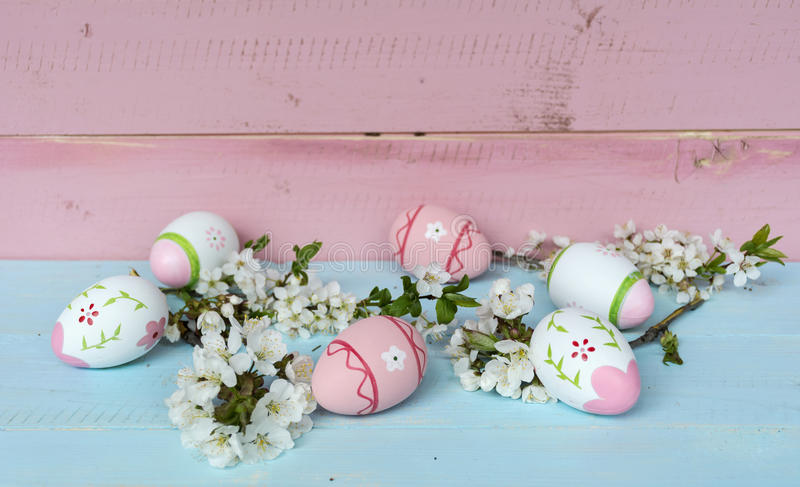 Pink easter eggs and cherry blossoms on a blue wooden background. Pink easter eggs and cherry flowers on a wooden background .Easter decoration royalty free stock photos