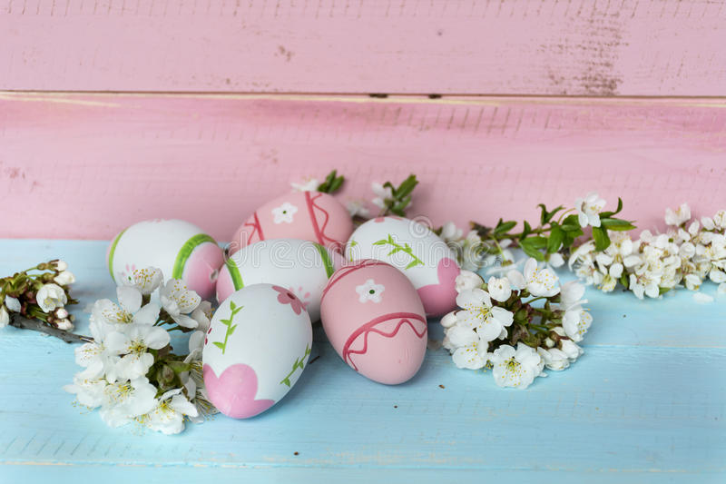 Pink easter eggs and cherry blossoms on a blue wooden background. Pink easter eggs and cherry flowers on a wooden background .Easter decoration stock image