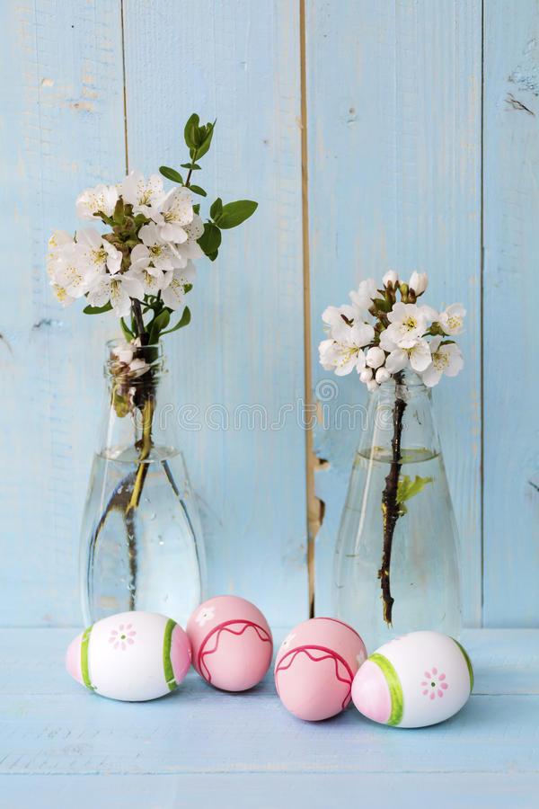 Pink easter eggs and cherry blossoms in vases on a blue wooden background stock photography