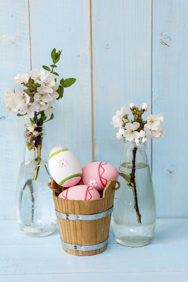 Pink easter eggs and cherry blossoms in vases on a blue wooden background. Pink easter eggs and vases with blooming cherry on a wooden background .Easter stock image