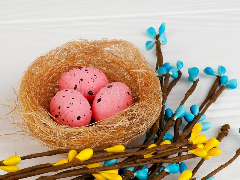pink Easter eggs in nest on white wooden background, copy space stock images