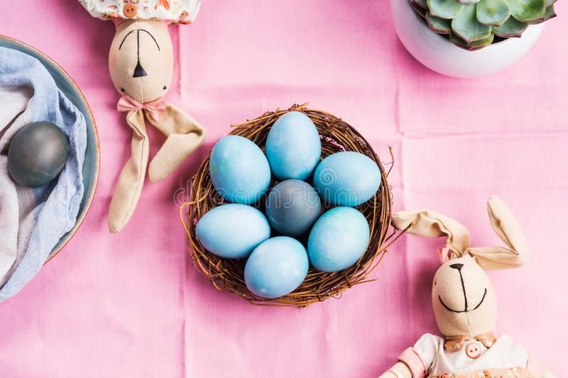 Pink easter holiday concept with bunnies and eggs. Pink easter holiday concept with bunnies and blue colored hard boiled eggs in a basket. Table decor flat lay royalty free stock photo