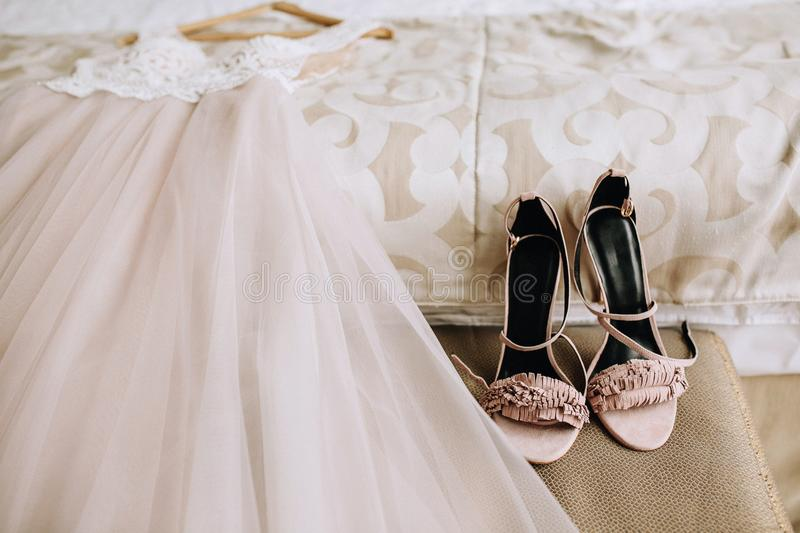 Pink elegant bride shoes next to a beautiful wedding dress lies on the bed in a hotel room. Wedding preparation stock photo