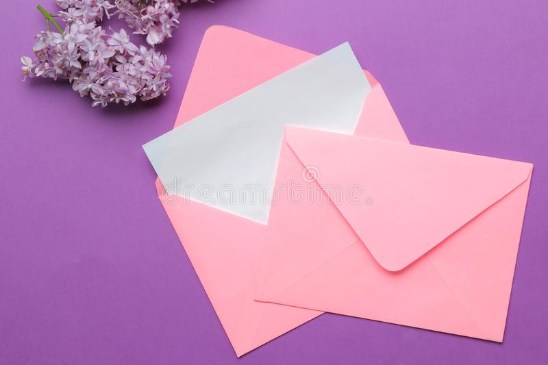 Pink envelope with a blank for the inscription and a sprig of lilac on a bright trendy lilac background. top view royalty free stock photos