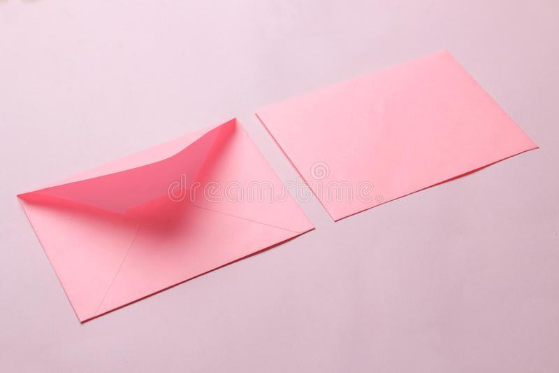 Pink envelope with a blank for text on a bright trendy pink background. free space stock photo