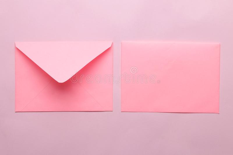 Pink envelope with a blank for text on a bright trendy pink background. top view royalty free stock image