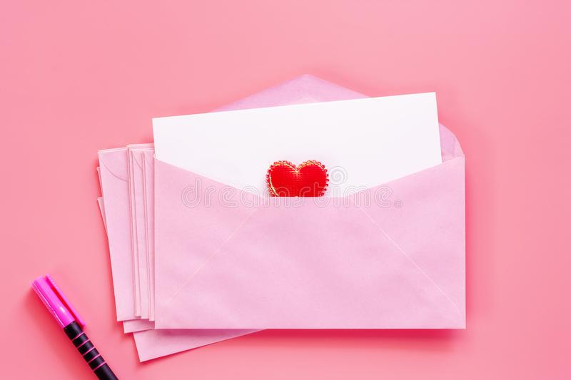 Pink envelope with blank white greeting paper card, red heart an royalty free stock images