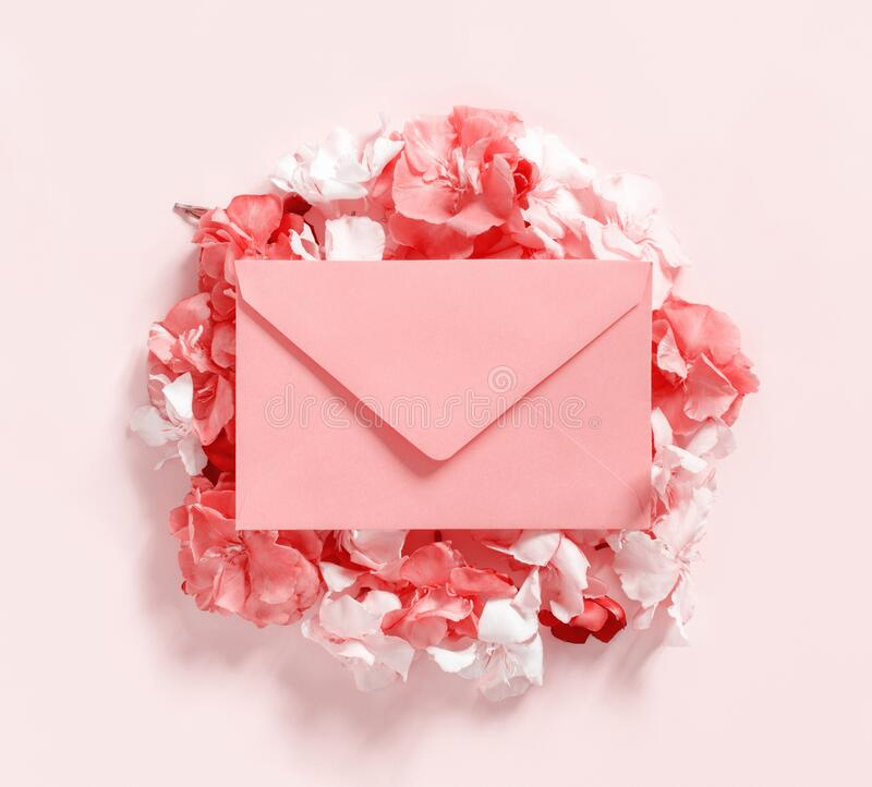 Pink envelope on flowers  over a pink background top view stock photos