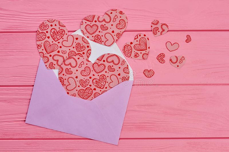 Pink envelope with heart shaped cutouts. royalty free stock photography