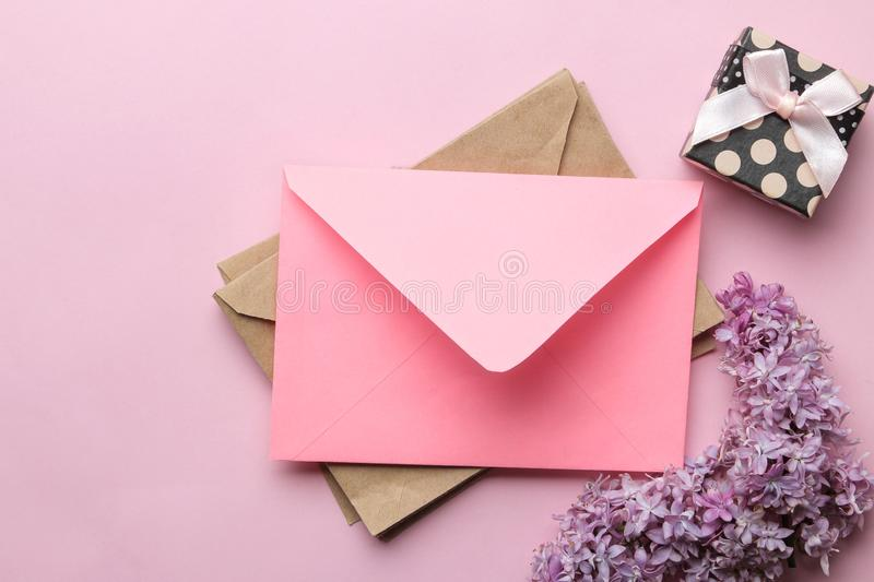 Pink envelope, lilac branch and gift box on a bright trendy pink background. top view royalty free stock photos