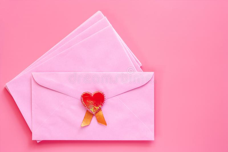 Pink envelope with red heart on pink background royalty free stock photo