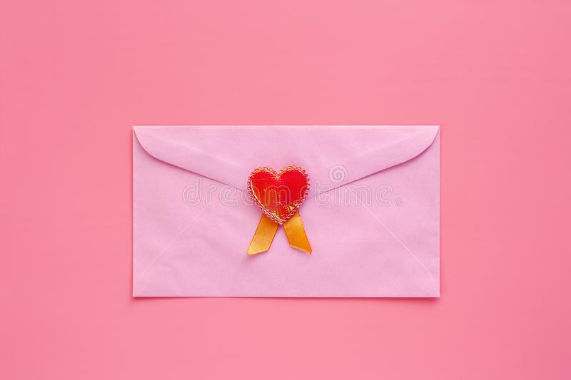 Pink envelope with red heart on pink background stock photography