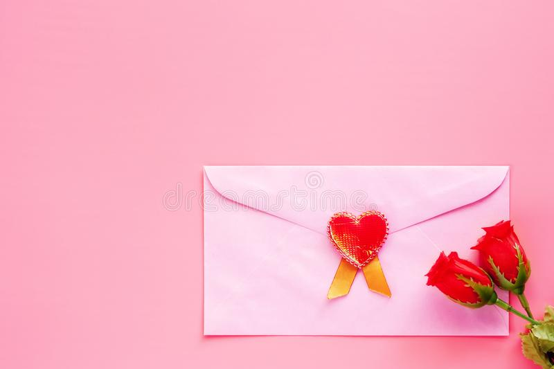 Pink envelope with red heart and rose flower on pink background stock images