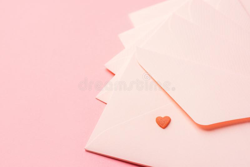 Pink envelopes arranged in fan with one small red candy heart on top on monochrome pastel background. Valentine love letters. Charity donation mother`s day royalty free stock photography