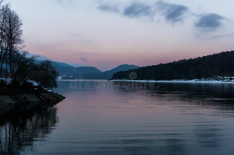 Pink evening sky at lake Walchensee. Serene and inspiring reflection, beautiful lake view stock photography