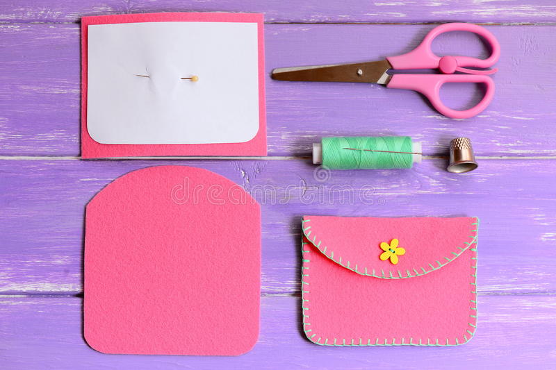 Pink felt purse with yellow flower button. Scissors, thread, needle, thimble, paper template, felt pieces on a wooden table. Simple handmade crafts for kids royalty free stock photos