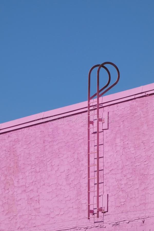 Fire Escape. A pink fire escape against a pink wall stock image