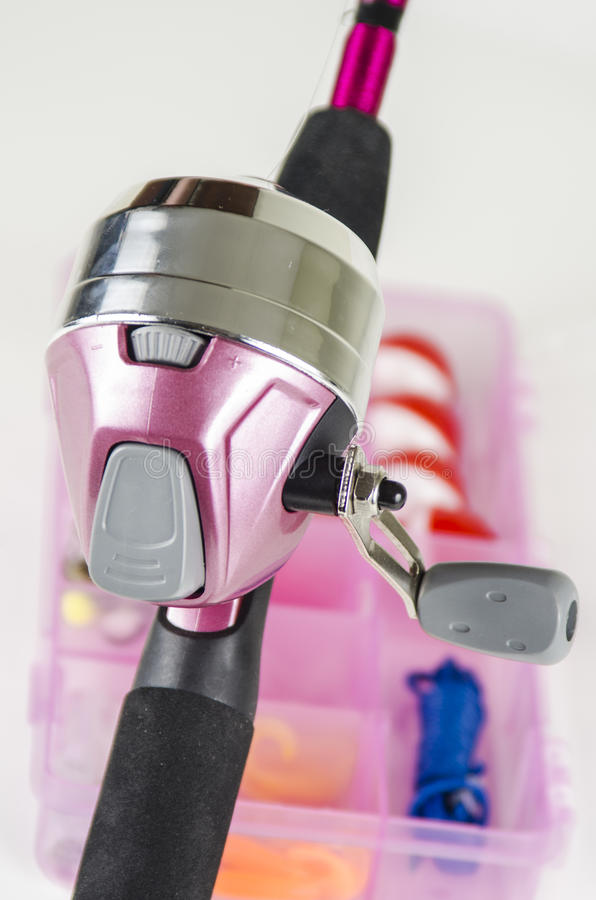 Pink Fishing Pole. Fishing pole and pink tackle gear box with awareness of breast cancer. Focus is on the fishing rod trigger. Shallow depth of field stock image