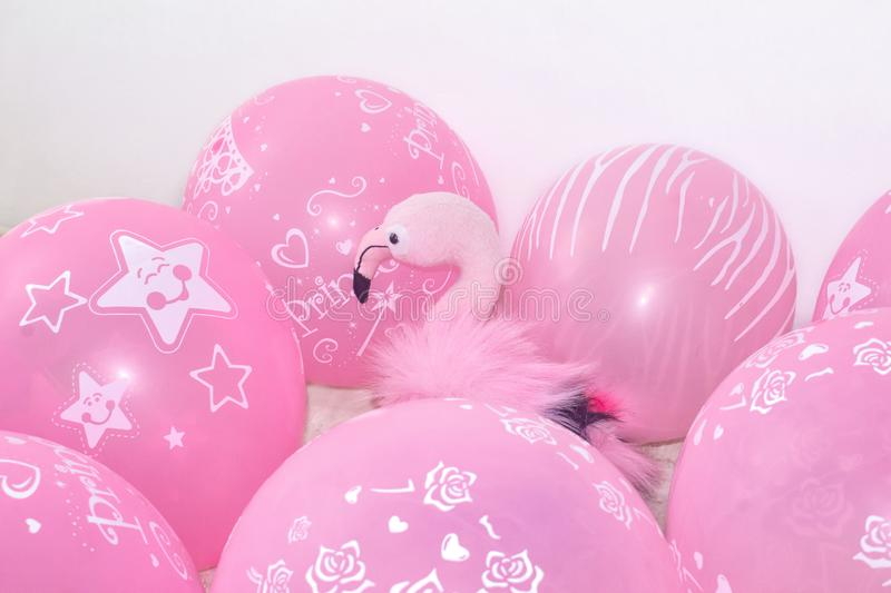 Pink flamingo, soft toy and balloons. The concept of holiday gifts and decorations. royalty free stock image