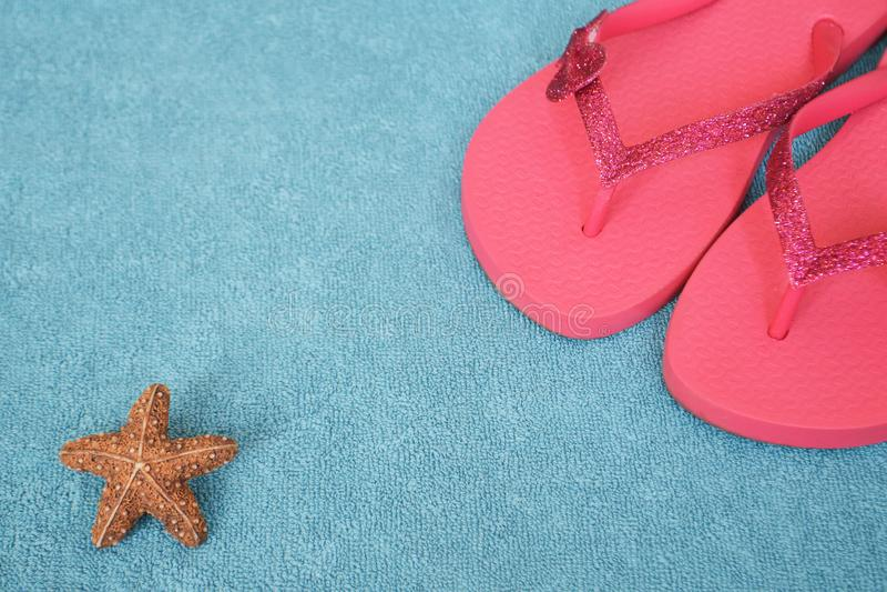 Flip flops on blue towel. Pink flip flops on blue towel stock photo