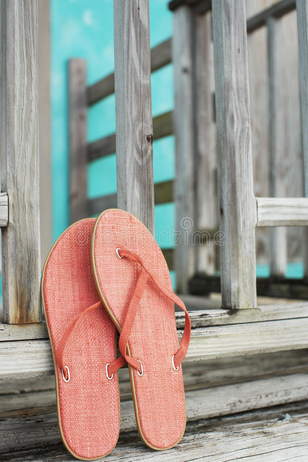 Pink flip flops leaning on fence stock images