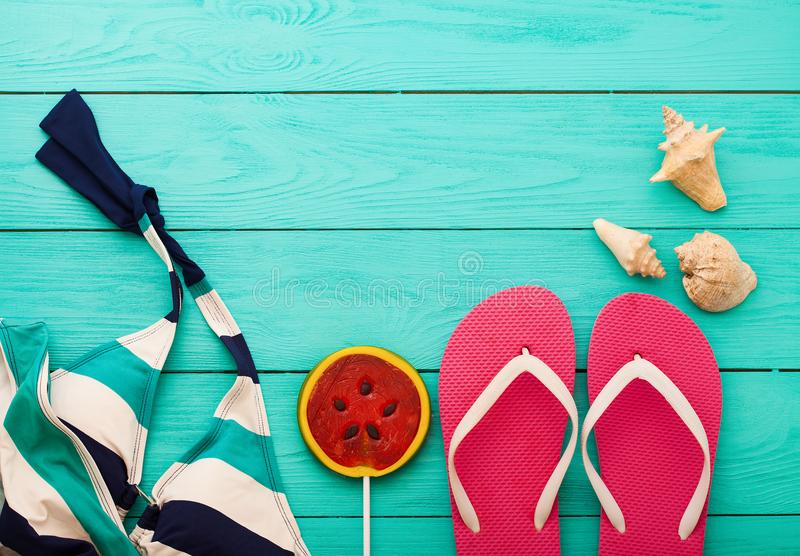 Pink flip flops, shells and summer swim suit with candy and copy space on blue wooden background. Top view royalty free stock image