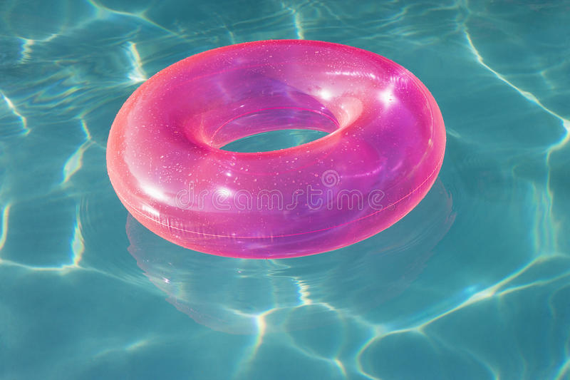 Pink Float Tube Floating in Swimming Pool royalty free stock photo