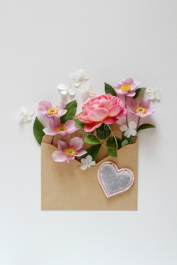 Pink floral composition in the brown envelope. On a white background stock photos