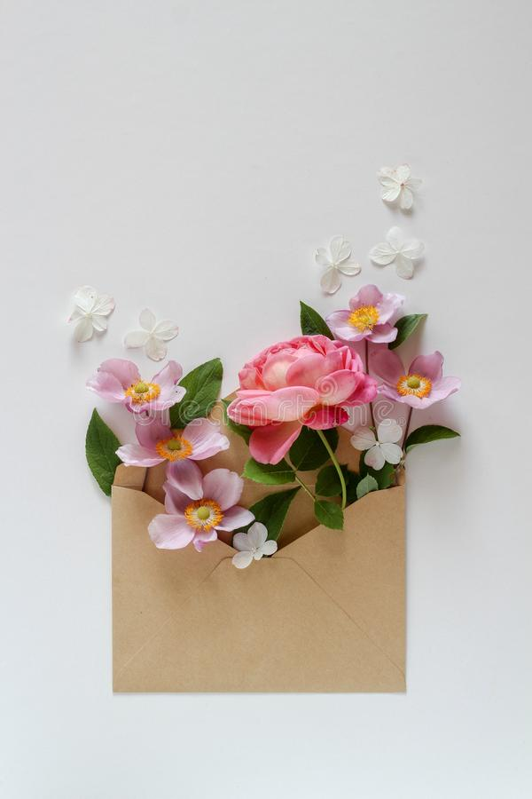 Pink floral composition in the brown envelope on a white background. Sending you flowers stock photos