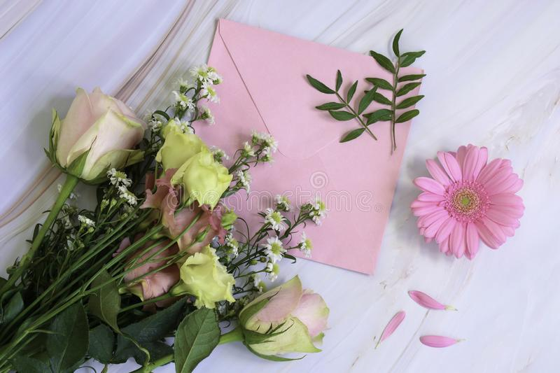 Pink floral composition with flowers, envelope and leaves on a marble background. Top view and flat lay style. Valentines day, mothers day, womens day, writing royalty free stock photography