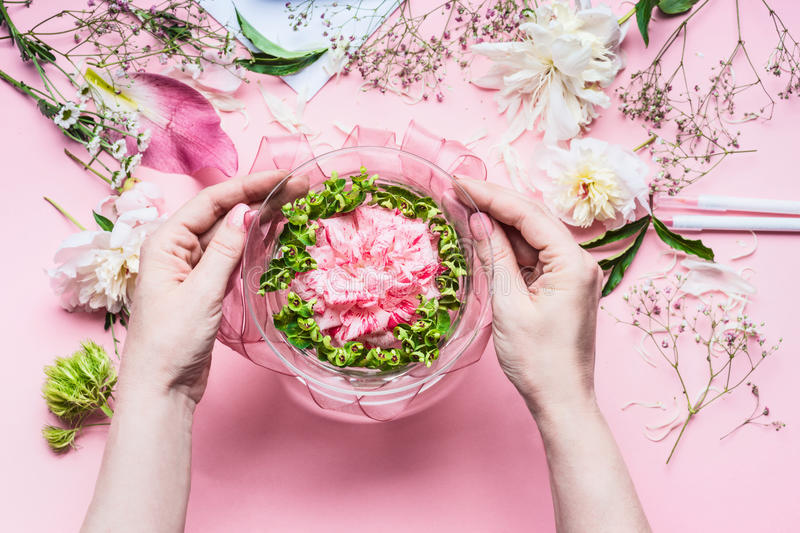 Pink Florist workspace with Lilies and other flowers, glass vase with water. Female hands making Festive Flowers arrangements. Top view royalty free stock photo
