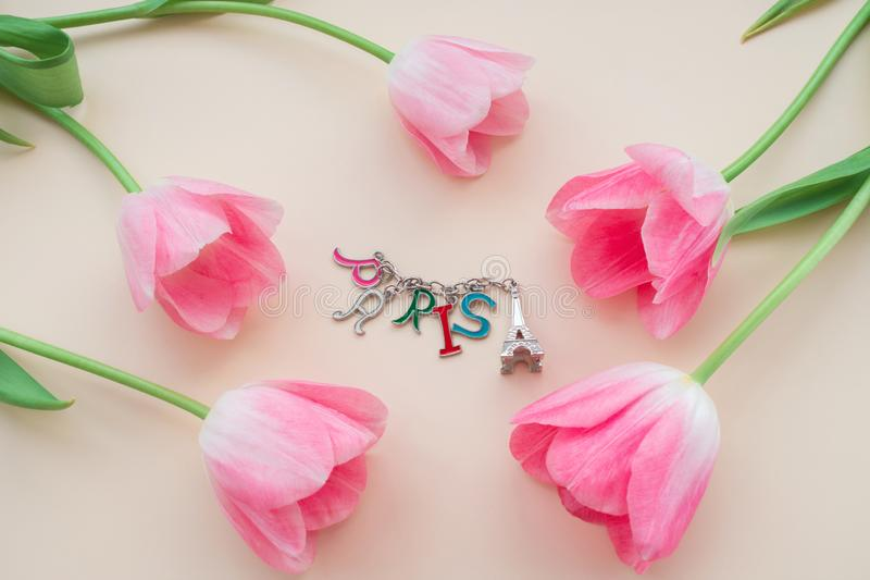 The pink flower buds around a keychain that looks like the Eiffel Tower with the inscription Paris. A close-up photograph of five pink flower buds around a stock photo