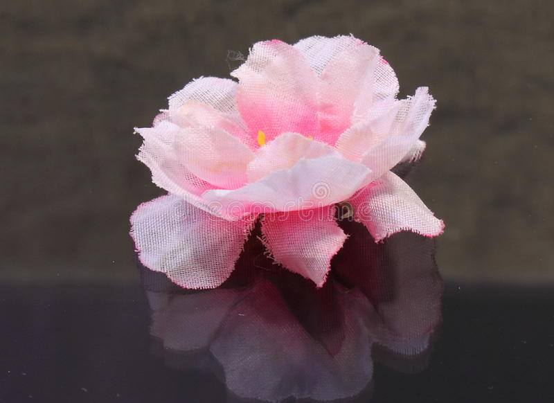Pink flower fabric. Handmade baby on the mirror surface stock images