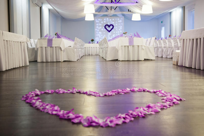 Pink flower petals heart on wedding dance floor. Photo of wedding reception room decorated in purple and white colors. At the foreground there is dance floor stock photography