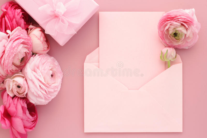 Pink flowers, blank card and gift box. Pink ranunculus flowers, envelope with blank greeting card. Birthday, Valentines Day, Mothers Day, Womens Day stock photos