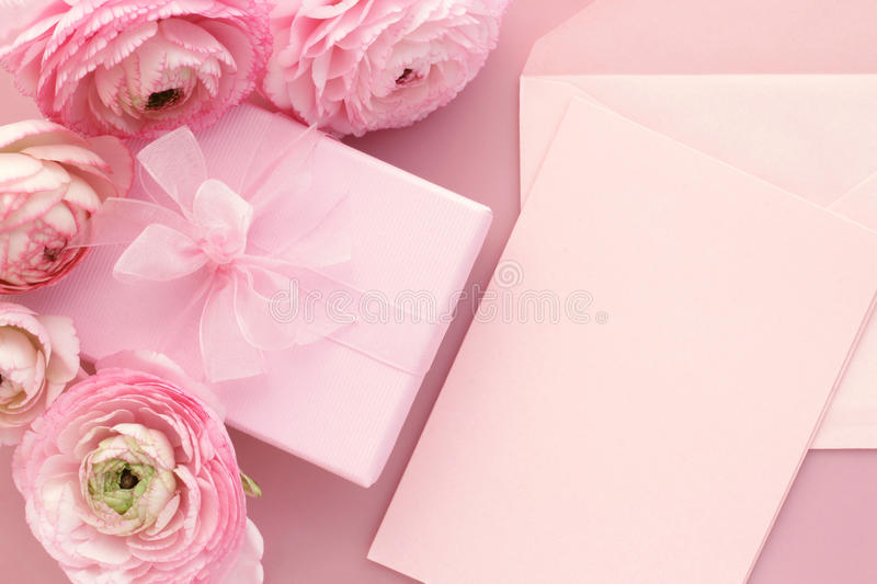 Pink flowers, blank card and gift box. Pink ranunculus flowers, opened envelope with blank greeting card. Birthday, Valentines Day, Mothers Day, Womens Day stock images