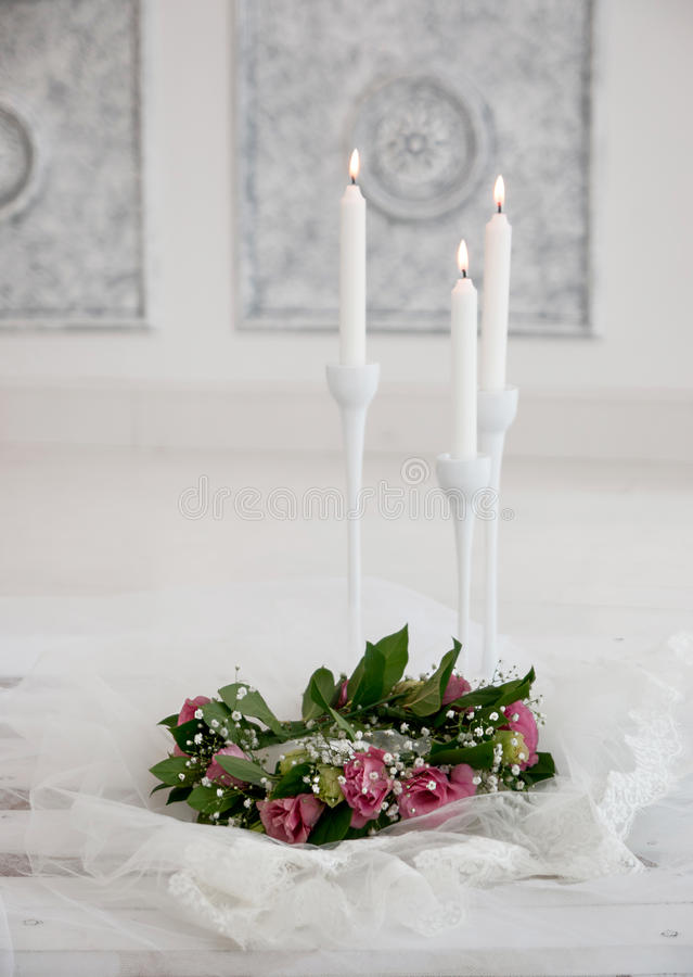 Pink flowers in the bouquet are near candles royalty free stock image