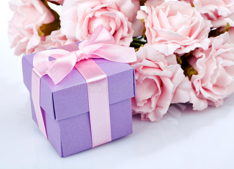 Pink flowers and gift box. Pink flowers and purple gift box with pink ribbon and bow on a white background royalty free stock images