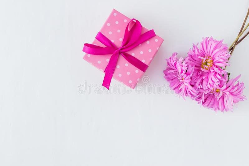 Pink flowers with gift box on white background. Empty space for your text, top view royalty free stock photo