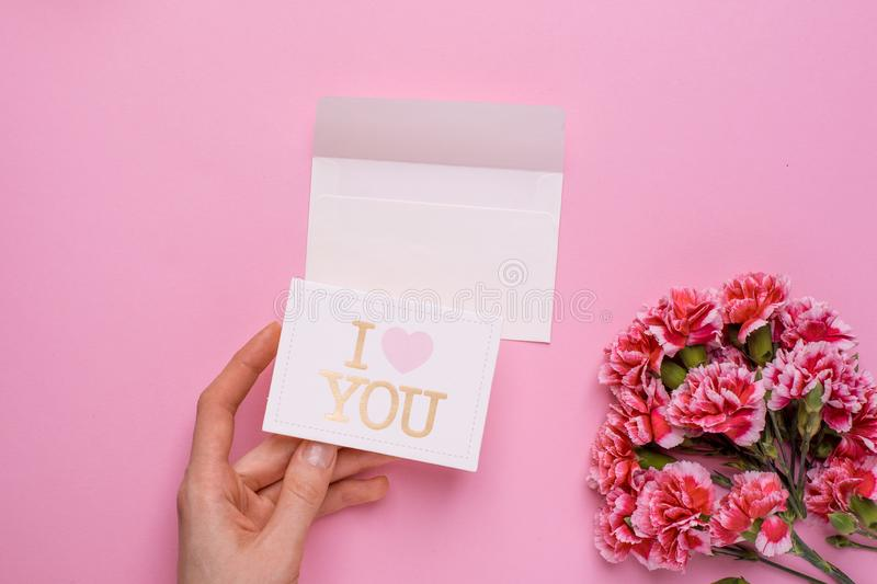 Pink flowers and hand with card I love you on a pink background. Top view royalty free stock photo