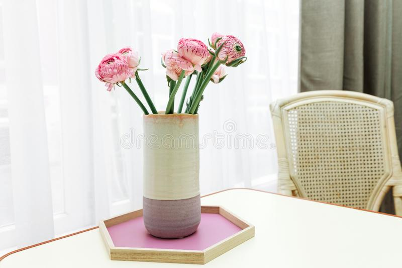 Aster bouquet vase table pink window white background lilac wicker chair stock images