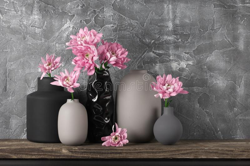 Neutral colored home decor. Pink flowers in neutral colored vases on distressed wooden shelf against rough plaster grey wall. Home decor stock image