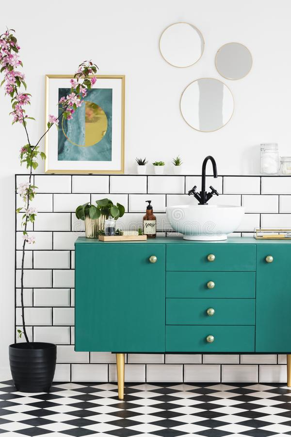 Pink flowers next to green cabinet in bathroom interior with posters and round mirrors. Real photo. Concept royalty free stock photography