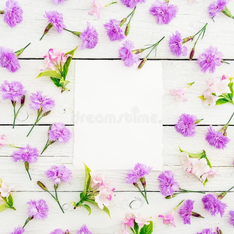 Pink flowers with paper card on white wooden background. Flat lay royalty free stock photography