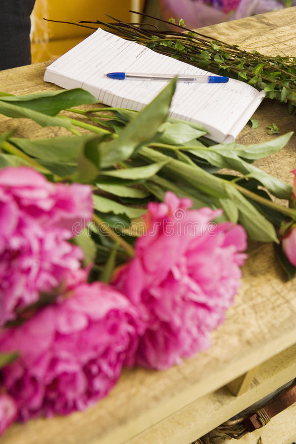 Pink flowers on table beside order pad in flower shop, close-up (still life) stock photos